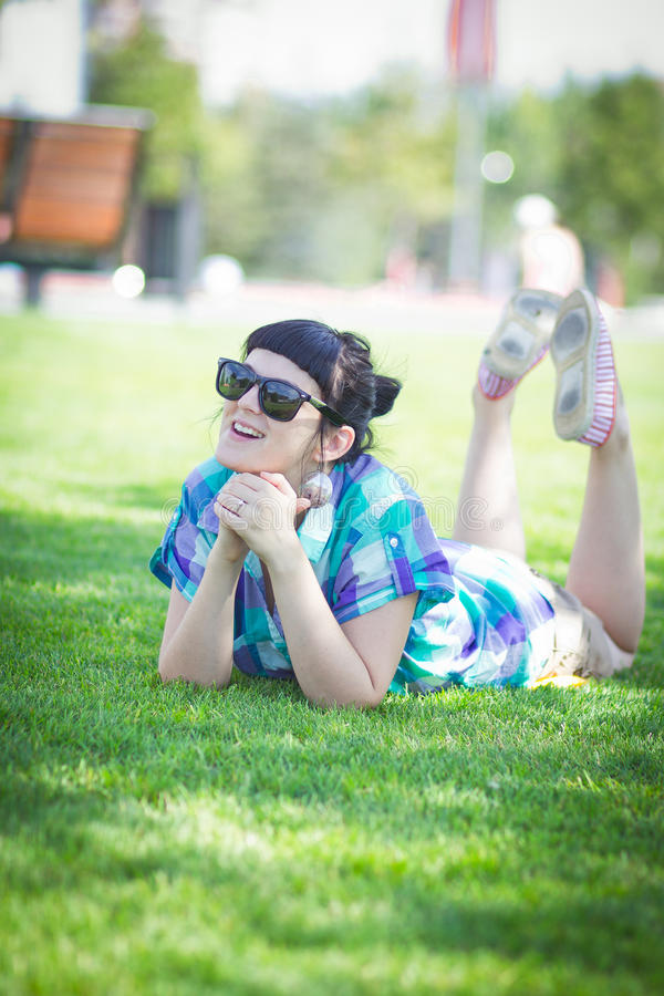 Pretty young woman lying on the green lawn stock photos