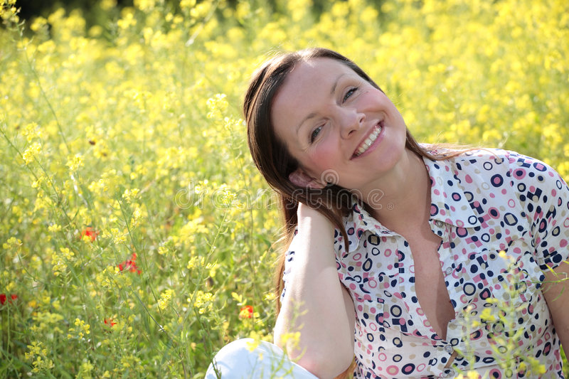 Pretty young woman on a meadow. Pretty young woman sitting on a meadow smiling royalty free stock photography