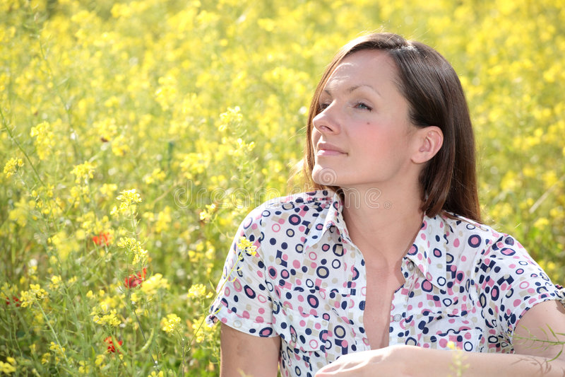 Pretty young woman on a meadow. Pretty young woman relaxing on a meadow smiling stock photography