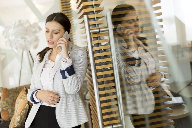Pretty young woman with mobile phone in the modern office stock photo