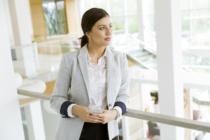 Pretty young woman with mobile phone in the modern office stock photos