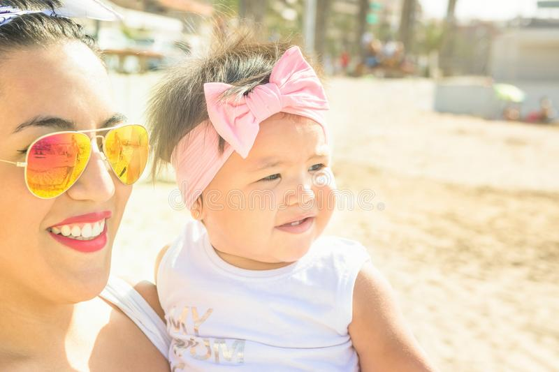 Pretty Young Woman Mother Holds Cute Smiling Baby Toddler Daughter in Hands Looking into Distance. Summer Sunlight. Genuine Candid stock photos