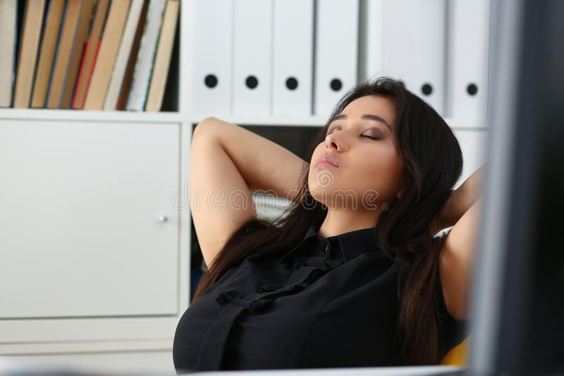 Pretty young woman in office sit at table finish all the work have a break can afford to relax. Pretty young chinese woman in office sit at table finish all the royalty free stock photography