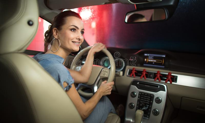 Pretty, young woman passing through a car wash. With her car stock photos