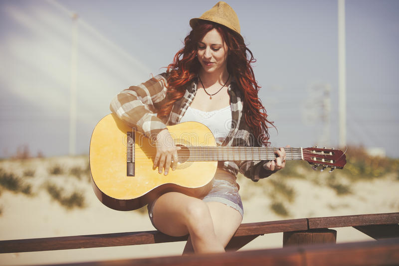 Pretty and young woman playing a guitar royalty free stock photo