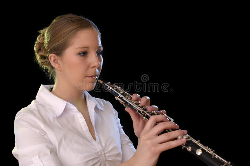 Pretty young woman playing Oboe stock image