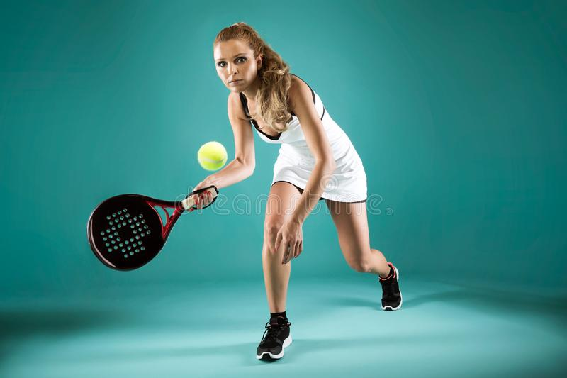 Pretty young woman playing padel indoor over green-blue background. stock image