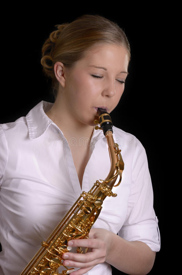Pretty young woman playing saxophone stock photo