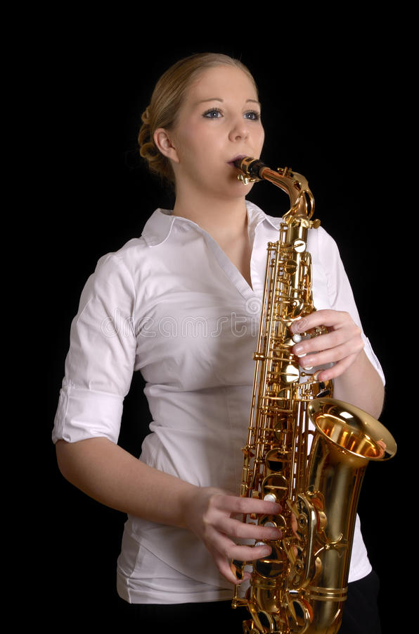 Pretty young woman playing saxophone royalty free stock photo