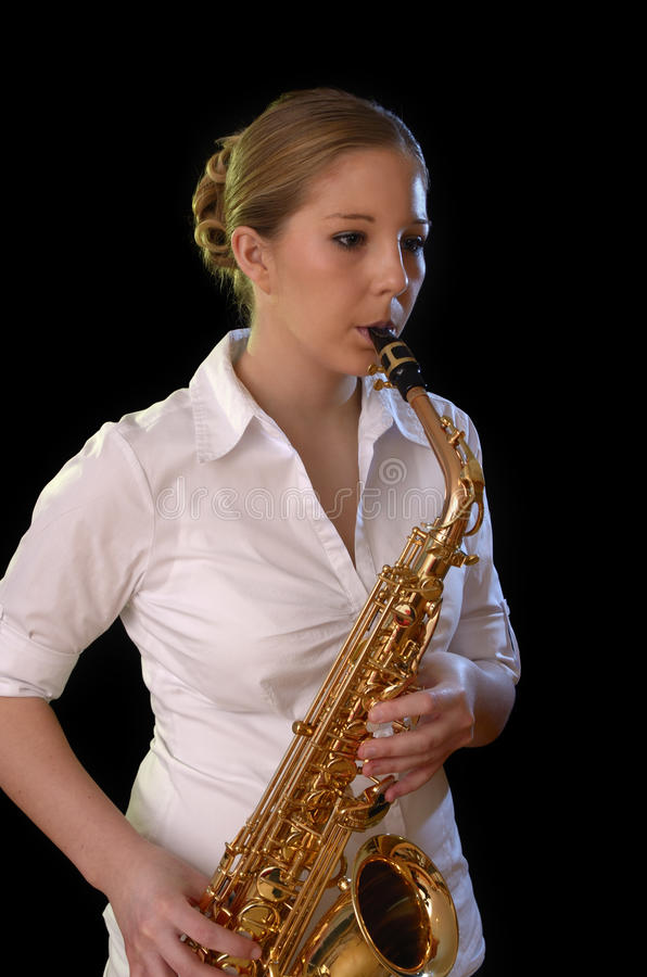 Pretty young woman playing saxophone royalty free stock image