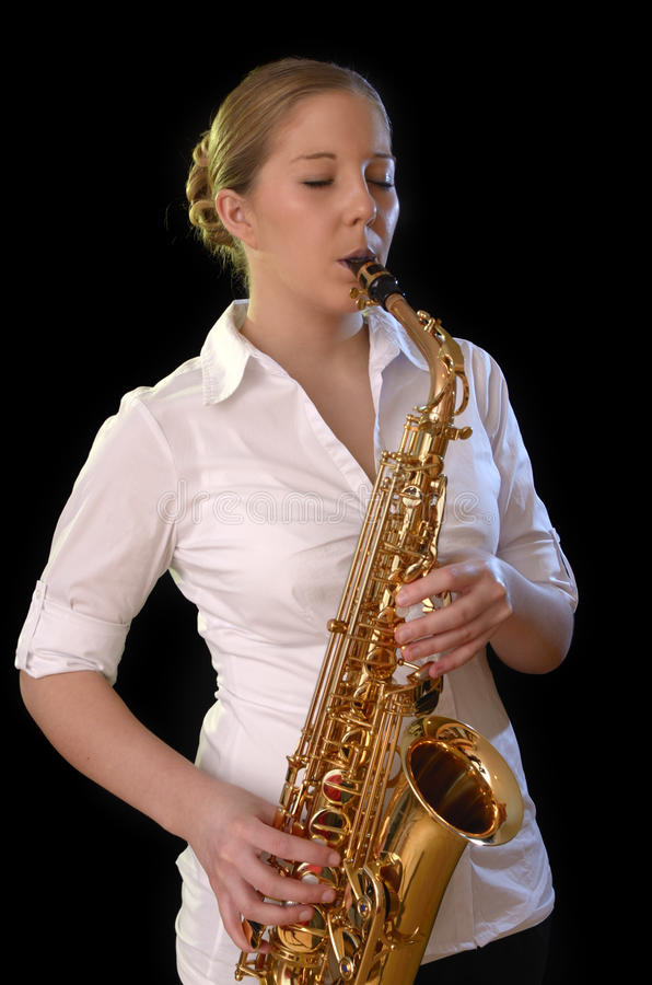 Pretty young woman playing saxophone stock photography