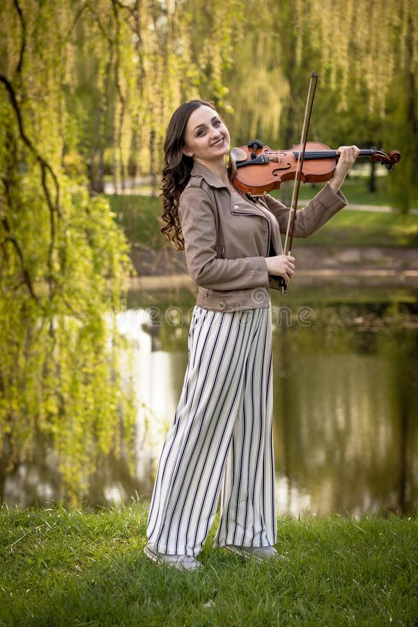 Pretty young woman playing the violin in the park and smiles, Full-length portrait stock photos