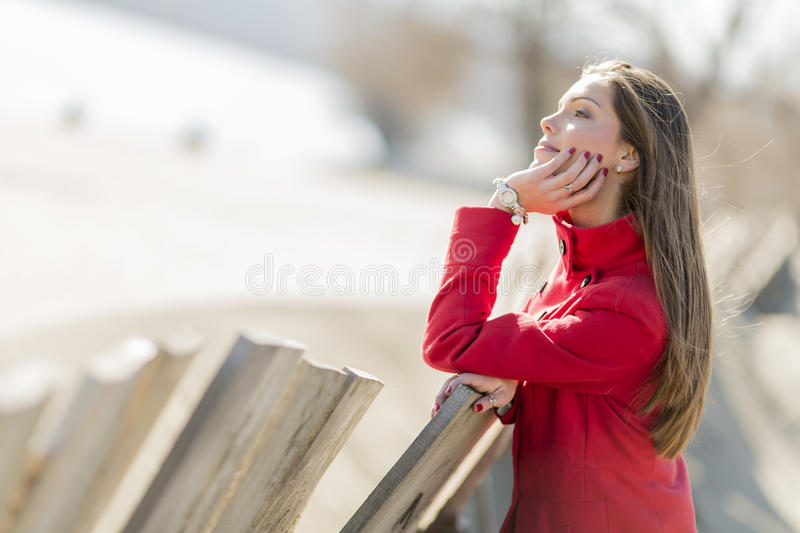 Pretty young woman in red coat stock photo