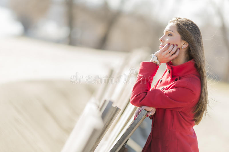 Pretty young woman in red coat stock photography