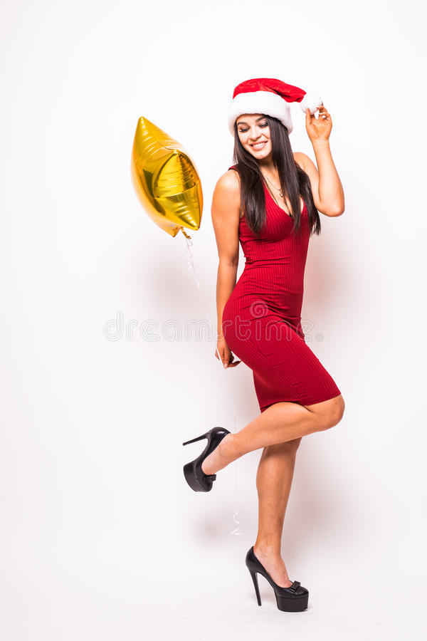 Pretty young woman in red dress and santa christmas hat with gold star shaped balloon stock photos