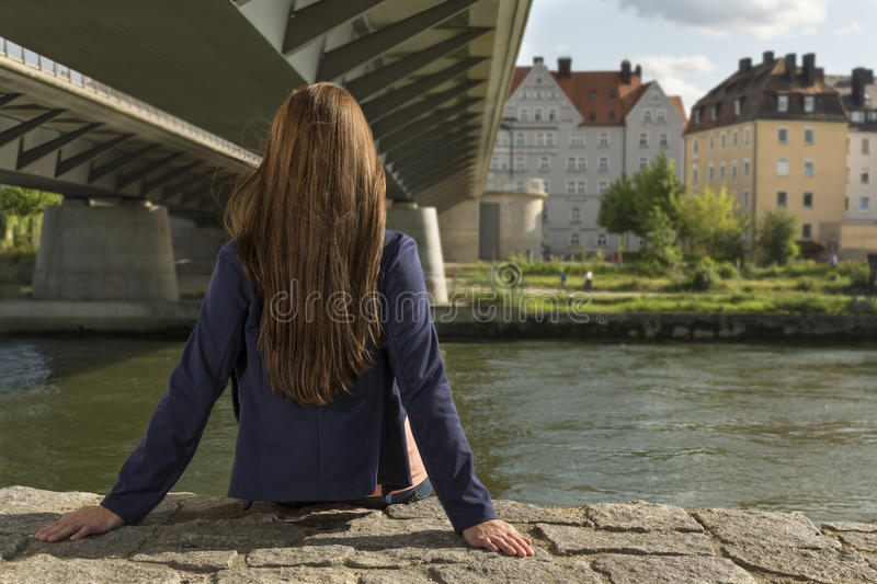 Pretty young woman relaxing at urban riverside stock image