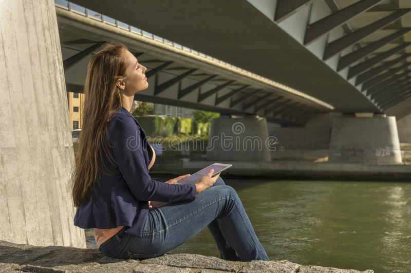 Pretty young woman relaxing at urban riverside stock images