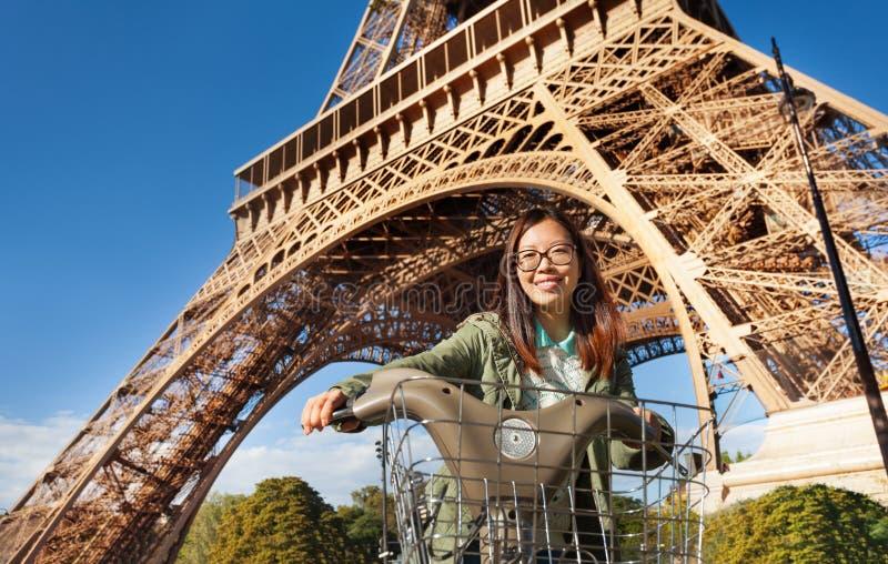 Pretty young woman riding bike near Eiffel Tower stock photo