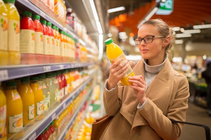 Pretty, young woman shopping for her favorite fruit juice royalty free stock image
