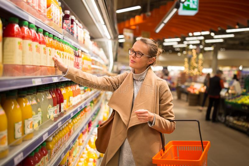 Pretty, young woman shopping for her favorite fruit juice. /smoothie at a grocery store stock photos