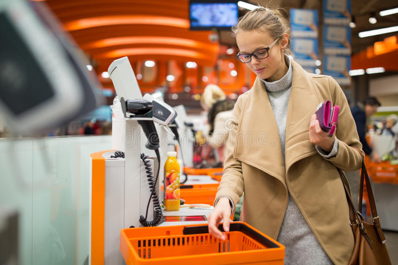 Pretty, young woman shopping for some fruit and smoothie. In a grocery store; paying for the goods at the self-service register color toned image stock photos