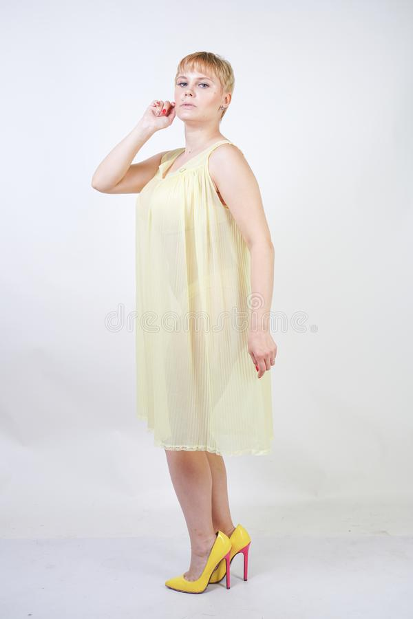 Pretty young woman with short hair and chubby body wearing transparent nightgown and posing on white studio background alone. beau stock image