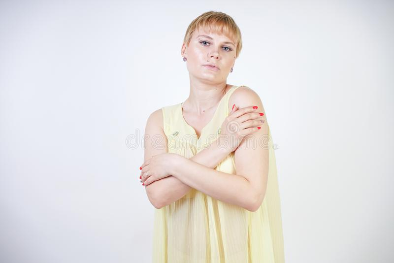 Pretty young woman with short hair and chubby body wearing transparent nightgown and posing on white studio background alone. beau stock photo