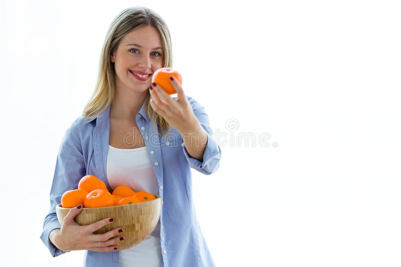 Pretty young woman showing orange to camera while holding a bowl over white background. Portrait of pretty young woman showing orange to camera while holding a stock photos
