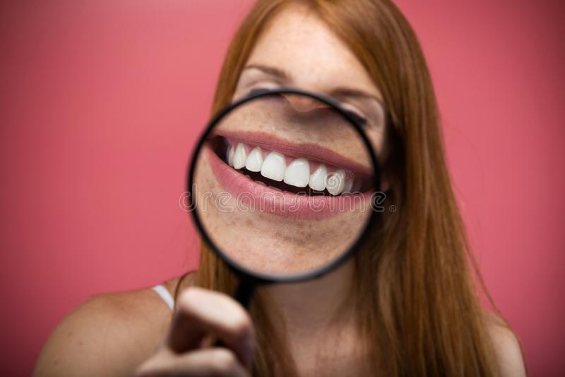Pretty young woman showing teeth trought magnifying glass over pink background. Portrait of pretty young woman showing teeth trought magnifying glass over pink royalty free stock photo