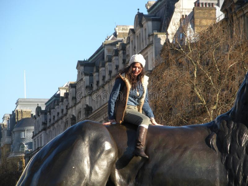 Fashionable Young Woman Poses Atop Bronze Lion, London, England, UK. A pretty young woman sits on top of one of the four bronze lions on the base of Nelson`s