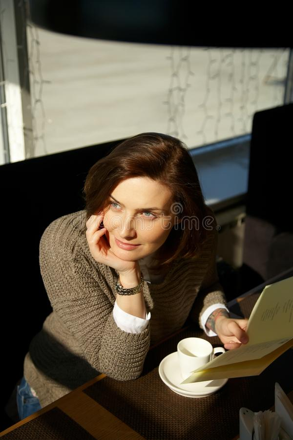Pretty young woman sitting in a cafe with cup of tea royalty free stock image