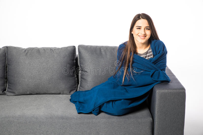Pretty young woman sitting on sofa covered with blanket on white royalty free stock image