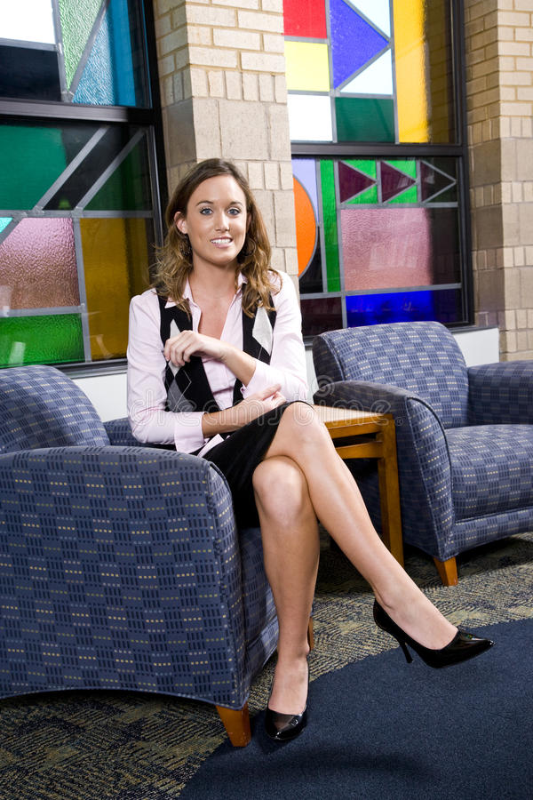 Pretty young woman sitting on waiting room chair royalty free stock image