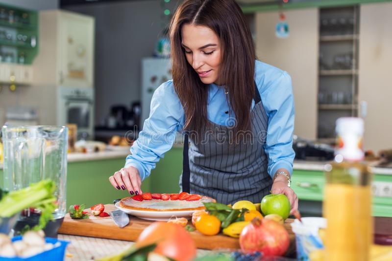 Pretty young woman smiling at camera while decorating a cake with sliced strawberry sitting in big kitchen royalty free stock photos