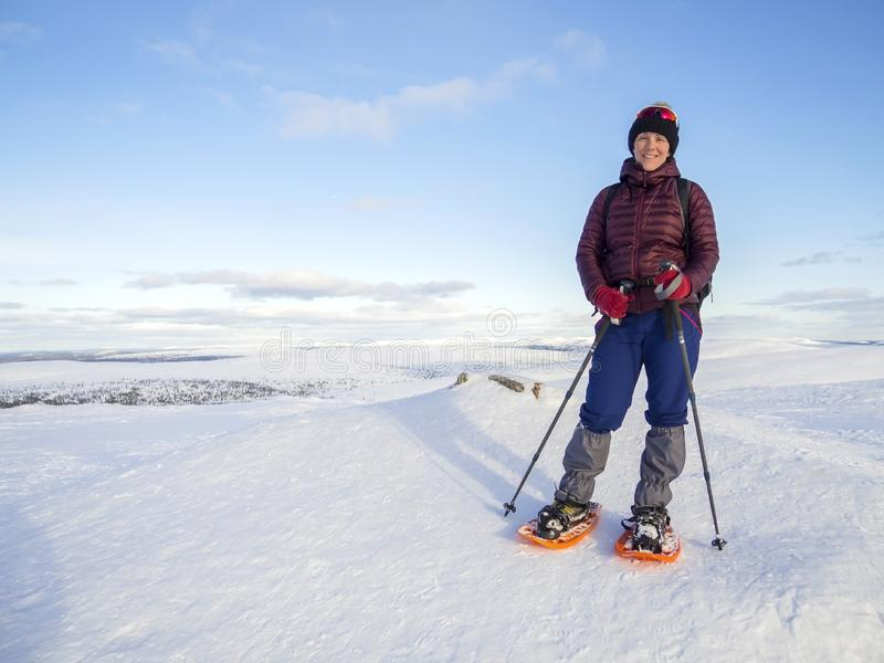 Pretty, young woman snowshoeing and enjoying splendid winter weather with abundance of snow royalty free stock photo