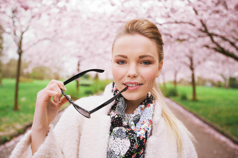 Pretty young woman at spring park with sunglasses. Pretty young woman at spring park holding sunglasses looking at camera. Caucasian female model posing at royalty free stock photo