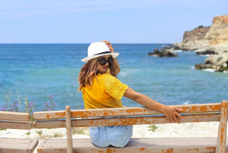 Pretty young woman in a straw hat sitting on a bench in front of the sea stock photography