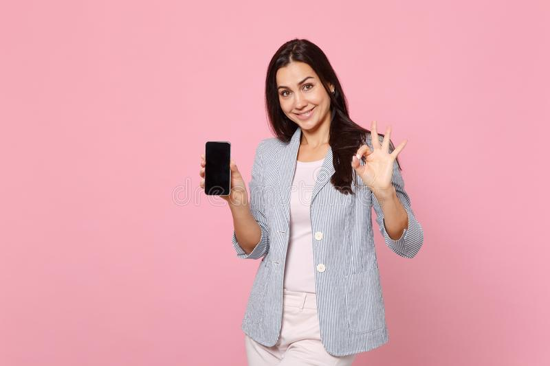 Pretty young woman in striped jacket showing OK gesture holding mobile phone with blank empty screen isolated on pink stock photo