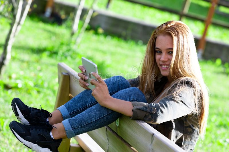 Pretty young woman student relaxing on a bench. Outdoors in a park with her legs up over the back smiling at the camera royalty free stock photos