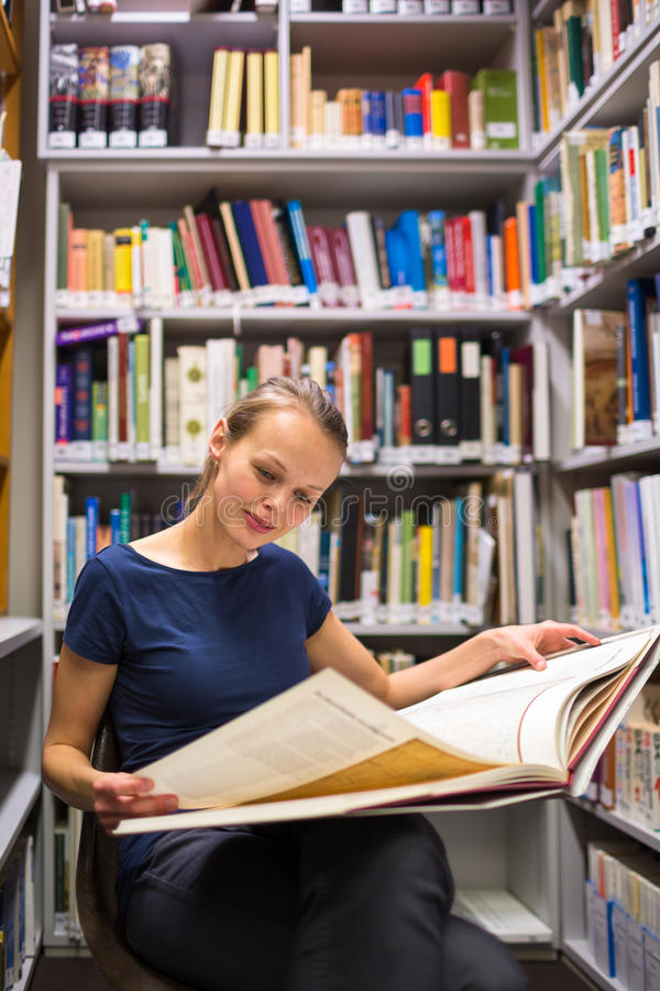 Pretty, young woman studying an old book. In archives stock photography
