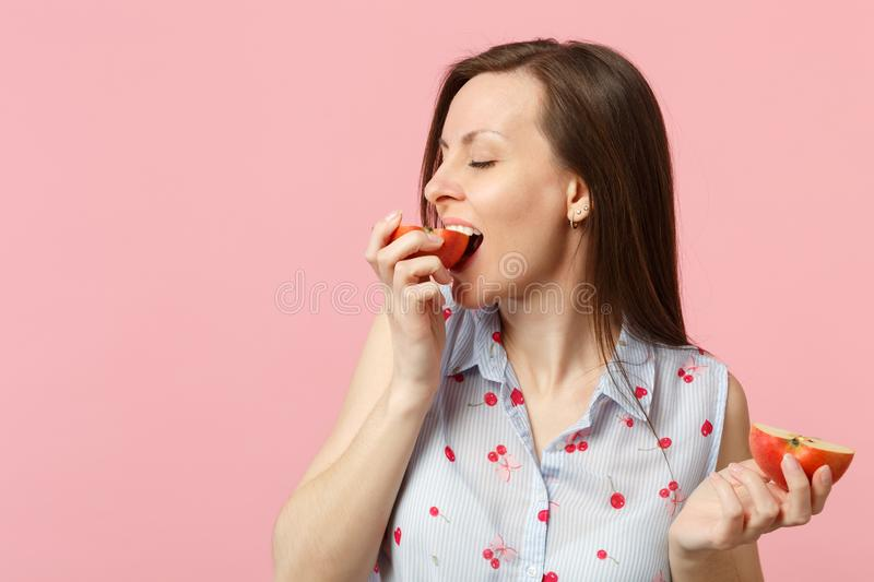 Pretty young woman in summer clothes holding, biting half of fresh ripe apple fruit isolated on pink pastel background royalty free stock images