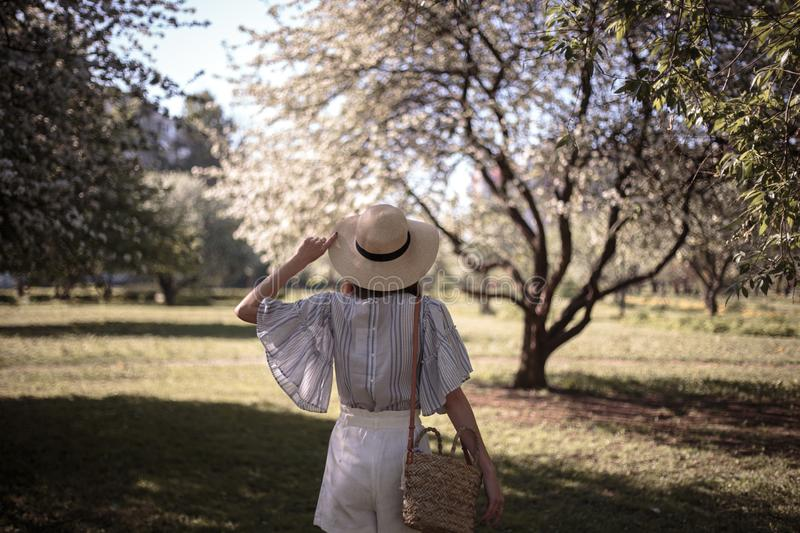 Pretty young woman in a summer garden, casual romantic style with hat. Natural makeup and hairstyle royalty free stock photos