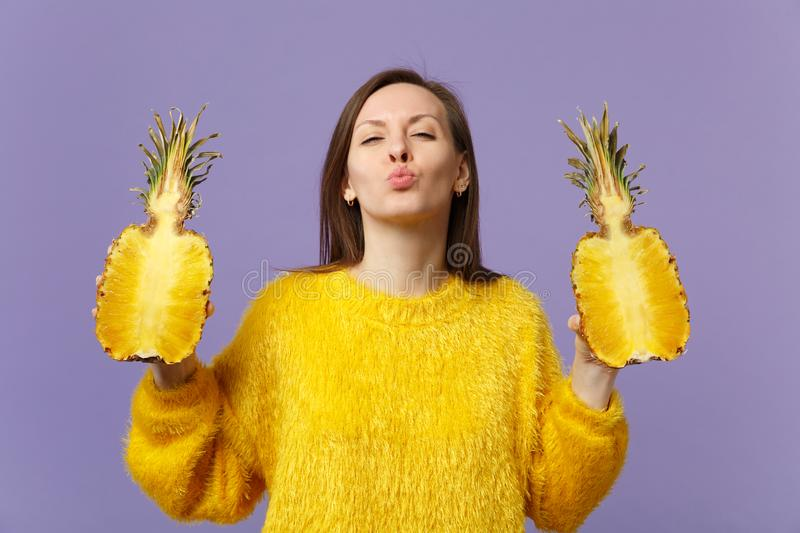 Pretty young woman in sweater blowing sending air kiss hold halfs of fresh ripe pineapple fruit isolated on violet. Pastel background. People vivid lifestyle royalty free stock photos