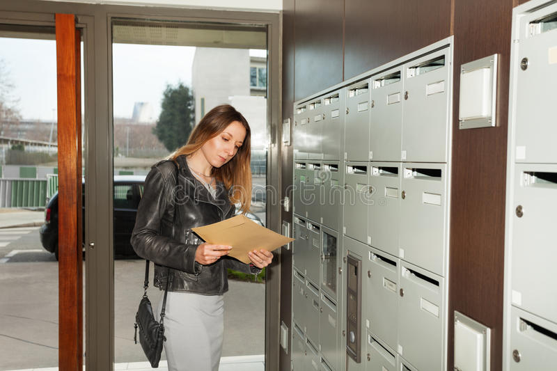 Pretty young woman taking envelope from mailbox stock images