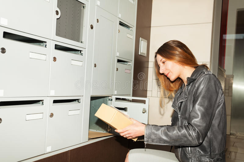 Pretty young woman taking package from mailbox royalty free stock photo
