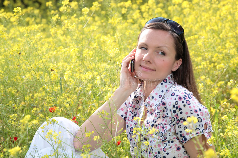 Pretty young woman talking on. Mobile phone on a meadow smiling gently stock image