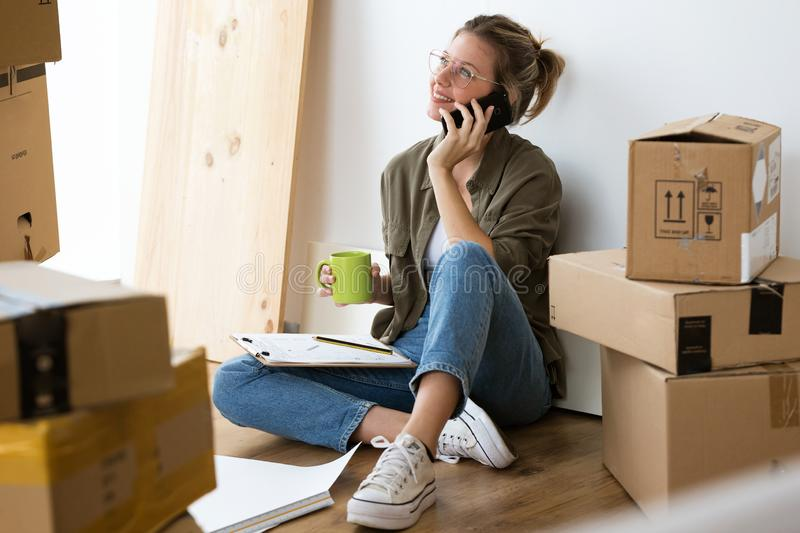 Pretty young woman talking on her mobile phone while sitting on hew new house. Shot of pretty young woman talking on her mobile phone while sitting on her new stock photography