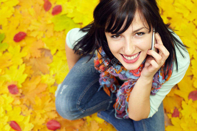 Download Pretty Young Woman Talking On Phone Among Leaves Stock Image - Image: 22373935