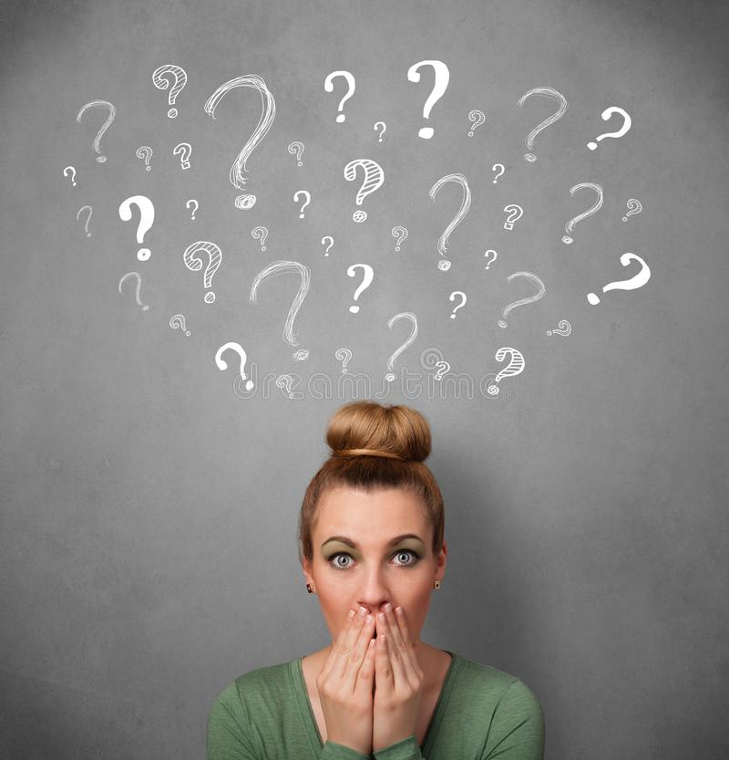 Young woman with question marks above her head. Pretty young woman thinking with sketched question marks all over her head royalty free stock photos