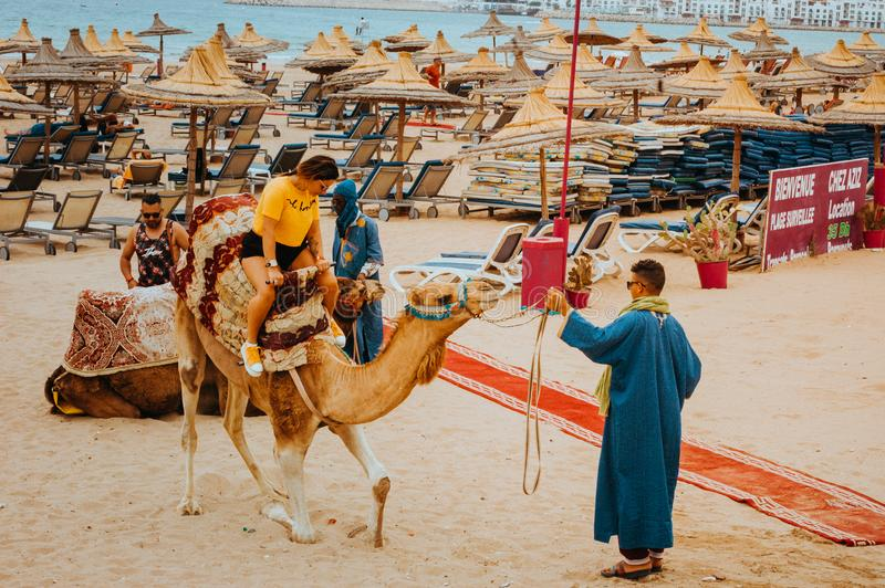 Pretty young woman tourist rides a camel for the first time stock photos